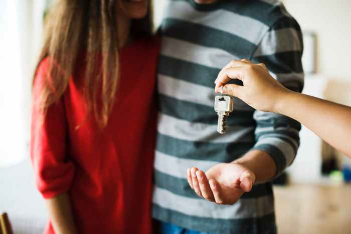 person giving keys on man