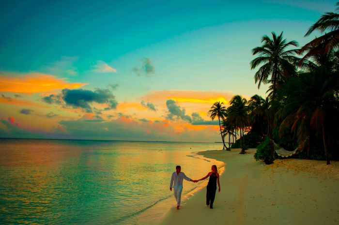 man and woman holding hand walking beside body of water during sunset