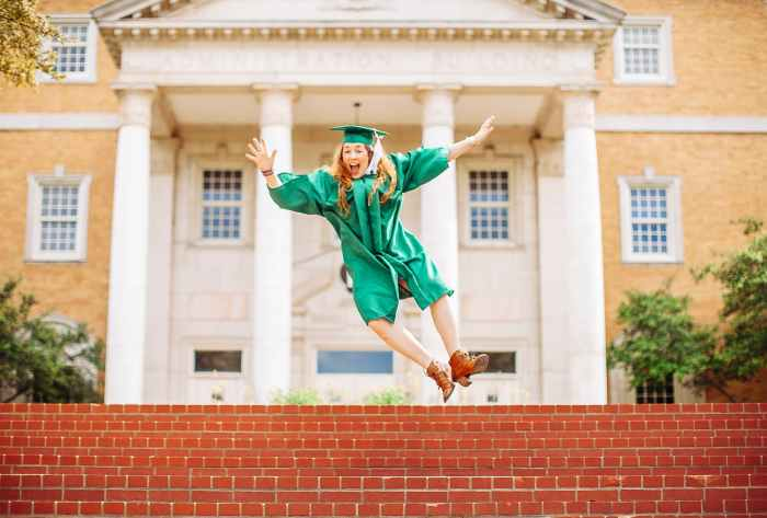 woman jumping above stairs wearing graduation gown and a hat
