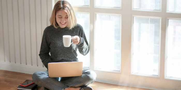 woman in gray sweater drinking coffee